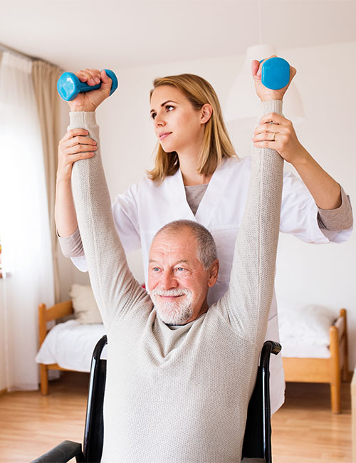 Health visitor and a senior man in a wheelchair during home visit. A nurse or a physiotherapist helping a senior man exercise with dumbbells.